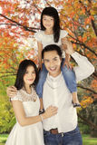 Asian family standing under autumn tree Royalty Free Stock Image