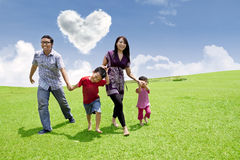 Asian family stroll. Happy asian family is having a stroll in the park under heart shape clouds stock image