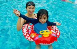 Asian family. In swim tube playing on swimming pool Stock Photography