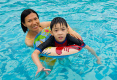Asian family. In swim tube playing on swimming pool Royalty Free Stock Images