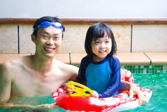Asian family. In swim tube playing on swimming pool Royalty Free Stock Photography