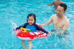 Asian family. In swim tube playing on swimming pool Royalty Free Stock Photos