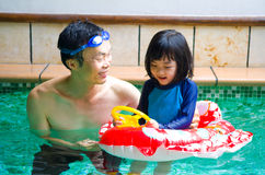 Asian family. In swim tube playing on swimming pool Stock Image