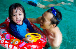 Asian family. In swim tube playing on swimming pool Royalty Free Stock Photo