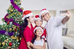 Asian family taking picture near Christmas tree. Asian family taking a selfie picture by using a smartphone near a Christmas tree. Shot at home Stock Image