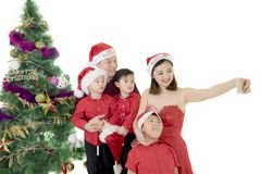 Asian family taking picture with Christmas tree. Asian family taking a selfie picture by using a smartphone while standing near a Christmas tree Royalty Free Stock Photo