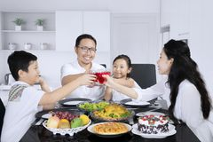 Asian family toasting glasses of syrup. Picture of Asian family toasting glasses of syrup together before having meals while sitting in the kitchen stock photo