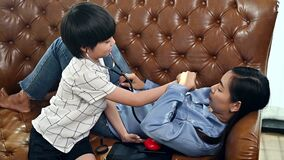 Asian family togetherness at home. Mom and kid playing as doctor together in living room. Lifestyle and family activity