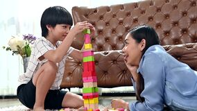 Asian family togetherness at home. Mom and kid playing wooden blocks in living room. Lifestyle and family activity
