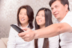 Asian family at TV with remote Stock Photography