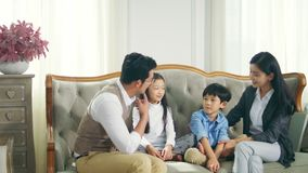Asian family with two children having fun at home. Happy asian family with two children sitting on couch chatting talking having fun stock video footage