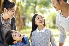 Asian family with two children having fun in park. Asian family with two children having fun exploring woods in a park royalty free stock photography