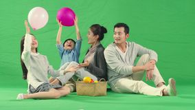 Asian family with two children having fun playing with balloons. Happy asian family with two children having fun playing with balloons, shot against green stock video