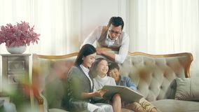 Asian family with two children reading book together