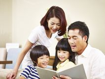 Asian family with two children reading a book together stock photo