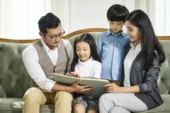 Asian family with two children reading book together. Asian parents and two children sitting on couch reading book together at home stock image