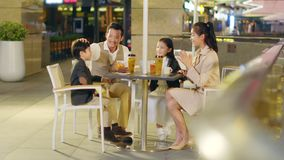 Asian family with two children relaxing in coffee shop. Happy asian family with two children chatting relaxing at a coffee place stock video