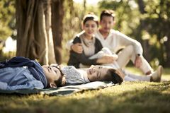 Asian family with two children relaxing in park. Two asian children little boy and girl having fun lying on grass with parents sitting watching in background royalty free stock photos