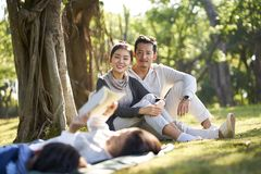 Asian family with two children relaxing in park. Two asian children little boy and girl having fun lying on grass reading a book with parents sitting watching in royalty free stock photography