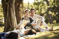 Asian family with two children relaxing in park. Two asian children little boy and girl having fun lying on grass reading a book with parents sitting watching in stock photos