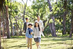 Asian family with two children relaxing in park. Asian family with two children walking relaxing having fun in park happy and smiling royalty free stock photography