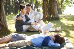 Asian family with two children relaxing in park. Young asian couple sitting on grass in park chatting with two children lying reading book in foreground royalty free stock photos