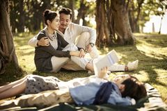 Asian family with two children relaxing in park. Young asian couple sitting on grass in park chatting with two children lying reading book in foreground stock photos