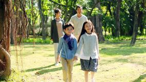 Asian family with two children relaxing in park. Asian family with two children relaxing walking in park stock video footage