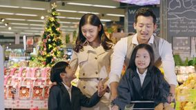 Asian family with two children shopping in supermarket. Asian family with two children talking while leaving a supermarket store with a shopping cart full of stock video