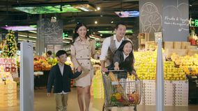 Asian family with two children shopping in supermarket. An Asian family with two children talking while leaving an Supermarket store with a shopping cart full of stock video