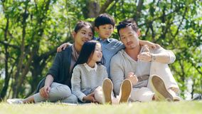 Asian family with two children relaxing outdoors. Asian family with two children sitting on grass outdoors in a park talking chatting stock footage