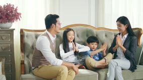 Asian family with two children having fun at home. Asian family with two children sitting on sofa having fun in living room at home stock video footage