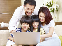 Asian family with two children using laptop together. Happy asian family with two children sitting on couch at home using laptop computer together Stock Images