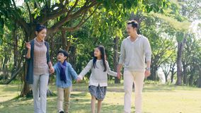 Asian family with two children relaxing in park. Asian family with two children walking hand in hand chatting in park stock video footage