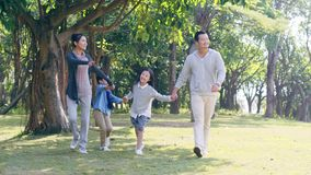 Asian family with two children walking in park. Asian family with two children walking hand in hand having fun in park stock footage