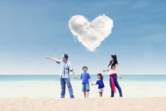 Asian family under heart cloud at beach Royalty Free Stock Photos