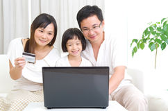 Asian family. Using laptop to perform online shopping royalty free stock photography