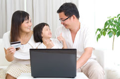 Asian family. Using laptop to perform online shopping Royalty Free Stock Images