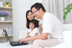 Asian family. Using laptop to perform online shopping Royalty Free Stock Photos