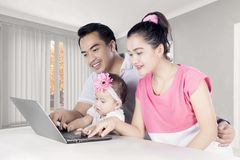 Asian family using a laptop together at home Royalty Free Stock Photography