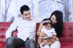 Asian family using tablet on couch Stock Images