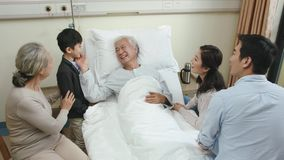 Asian family visiting grandfather in hospital
