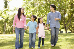 Asian family walking hand in hand in park Royalty Free Stock Images