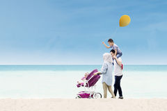 Asian family walking together on the shore Royalty Free Stock Photos