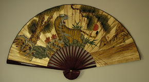 Asian Fan 1. A large decorative asian fan, hanging on a white wall. The fan has a scene painted on a gold background, with a tiger roaring Royalty Free Stock Photography