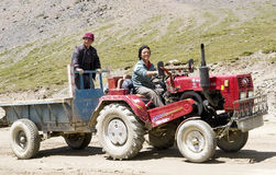 Asian farmer drives tractor. An asian farmer driver drives an old style tractor,smiling and another farmer on the tractor.Photo taken in Litang county ,Tibeta of Stock Images