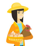 Asian farmer holding chicken and basket of eggs. Royalty Free Stock Images