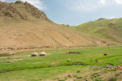 Asian farmer mobile homes and animals in a green sunny meadow. Mountain landscape with river curve, asian farmer mobile homes and animals in a green sunny meadow Stock Images