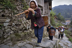 Asian farmers climb up mountain trail, with load on shoulders. Royalty Free Stock Images
