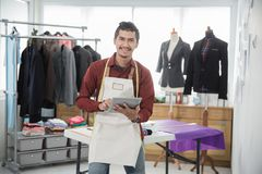 Asian fashion designer portrait smiling. Happy young asian fashion designer portrait with tablet smiling to camera while in his office Royalty Free Stock Image